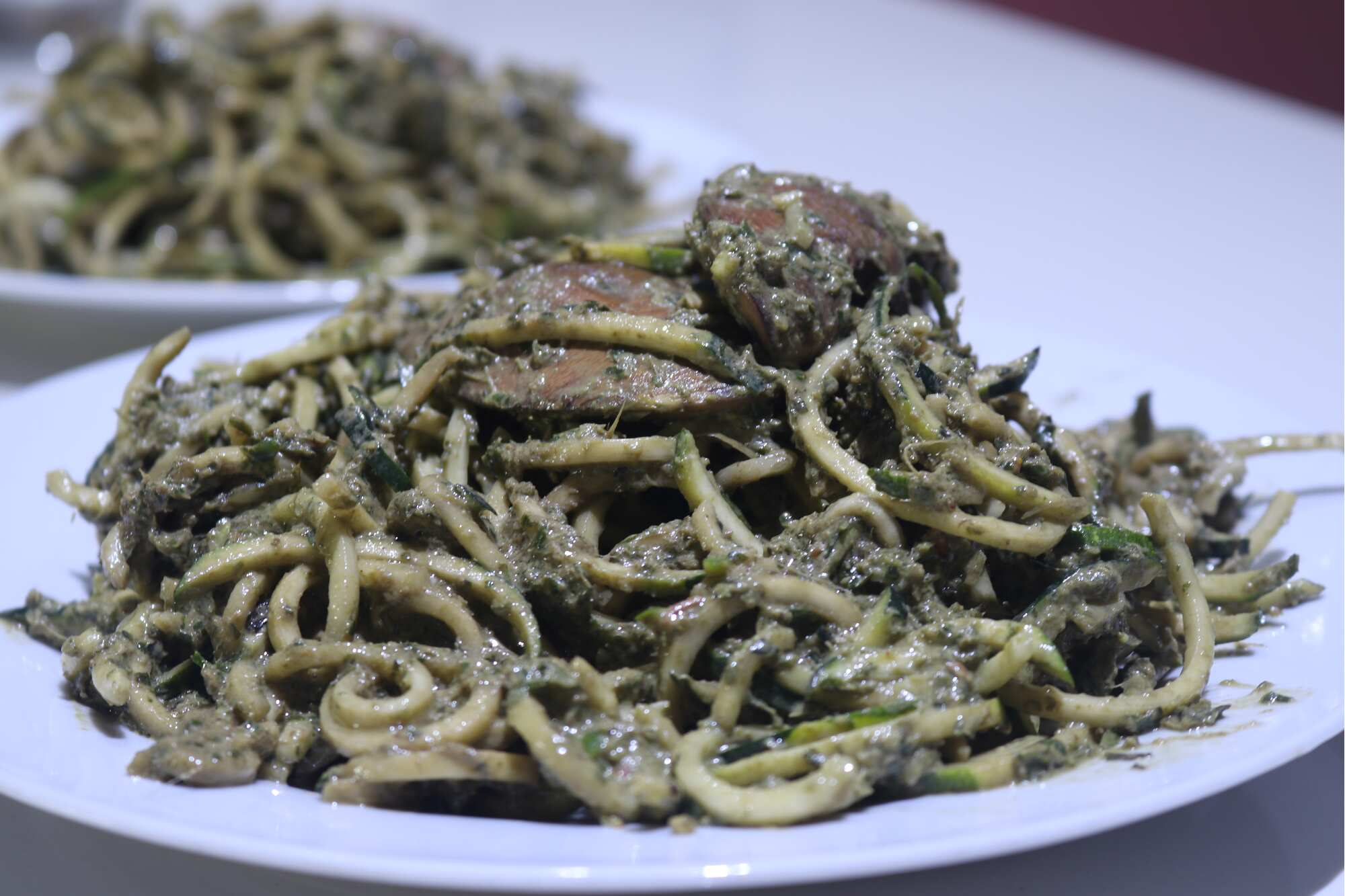 Zuchini Noodles with Basil Pesto topped with Portobelo Mushroom